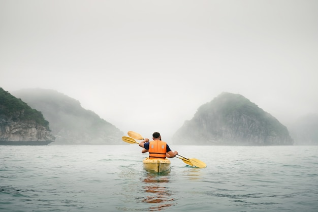 Paar paddelt das kajak bei nebelwetter
