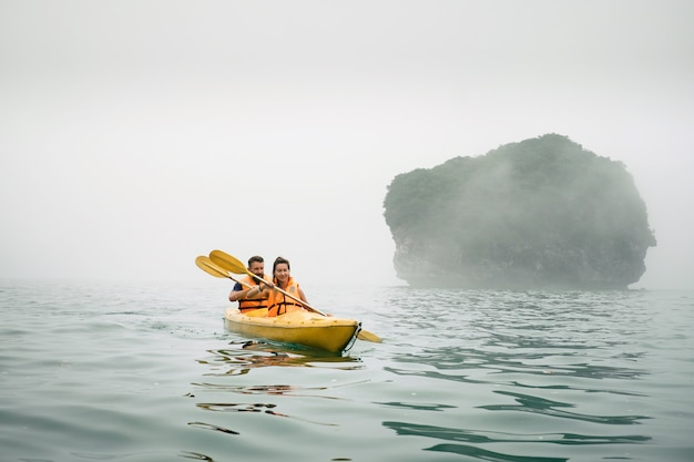 Paar paddelt das kajak bei nebligem wetter