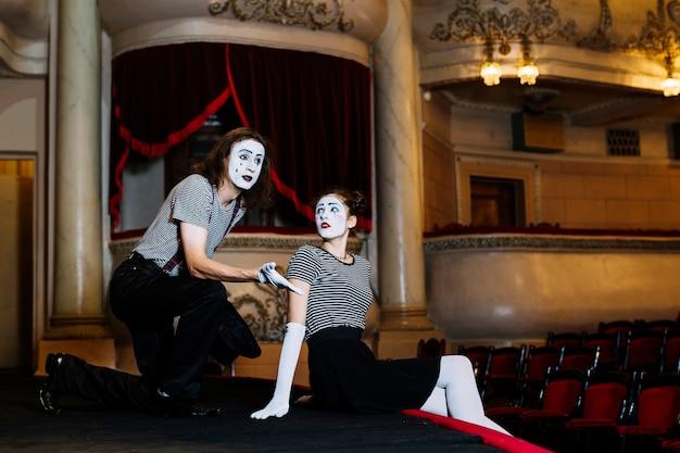 Paar pantomimekünstler, der am stadium im auditorium durchführt