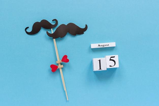 Paar papier schnurrbart requisiten befestigt herz und holz kalender 15. august