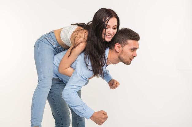 Paar posiert auf weißem hintergrund - mann mit frau auf dem rücken.