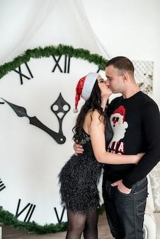 Paar posiert in der nähe der uhr mit mitternacht im studio