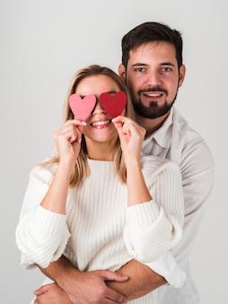Paar posiert mit herzen auf augen