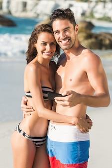 Paar posiert und hält smartphone