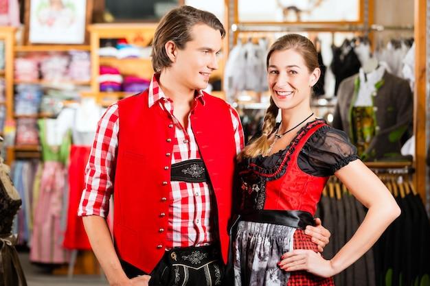 Paar probiert dirndl oder lederhosen in einem laden aus