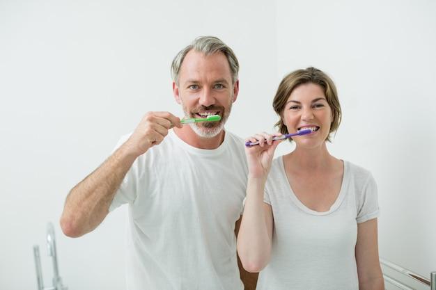 Paar putzen ihre zähne mit zahnbürste zu hause