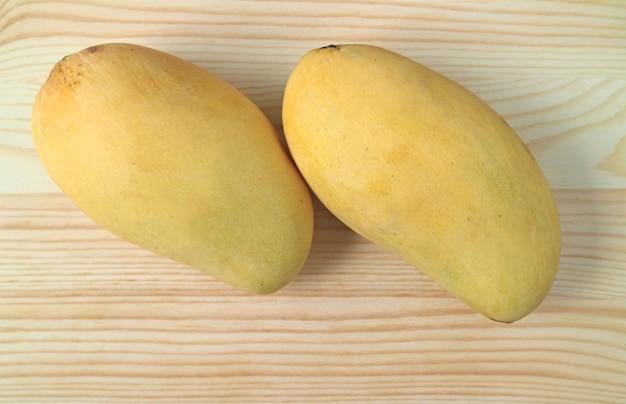 Paar reife ok-rong-mangos auf hölzernem hintergrund, süße und duftende mango in thailand