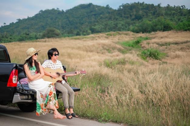 Paar reisende haben eine entspannende zeit während der fahrt neben der straße