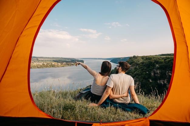 Paar reisende, mann und frau, die auf einer klippe in den bergen sitzen und landschaft beobachten.
