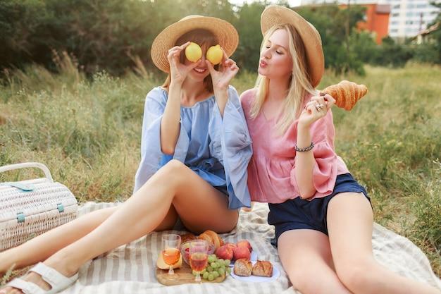 Paar reizende hübsche frauen, die auf rasen im sommerpark aufwerfen und leckeres essen, croissants und wein genießen. freunde genießen picknick.