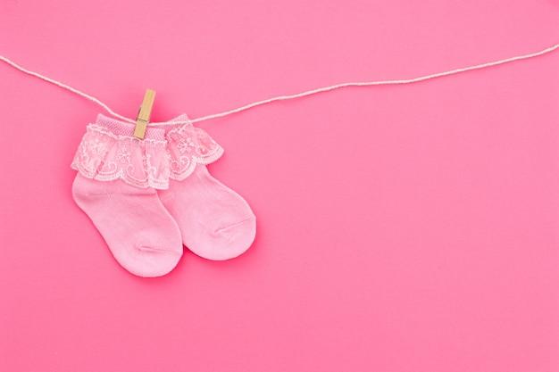 Paar rosa niedliche babysocken, die an der wäscheleine auf rosa hintergrund hängen. babyzubehör. flach liegen.