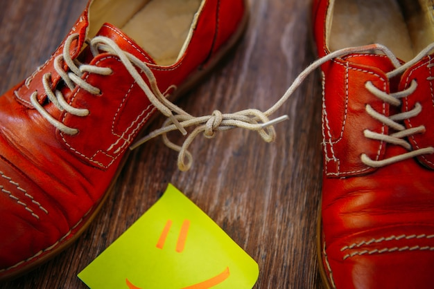 Paar rote schuhe auf hölzernem hintergrund. schnürsenkel zusammengebunden.