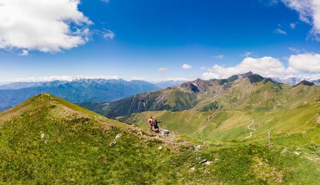 Paar rucksacktouristen, die auf berggipfel, landschaftlich reizvolle landschaft wandern. sommerabenteuer auf den alpen. eroberung erfolg erwachsener spaß spaß fitness fitness