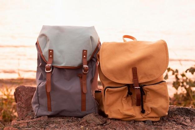 Paar rucksäcke auf felsen bei sonnenuntergang
