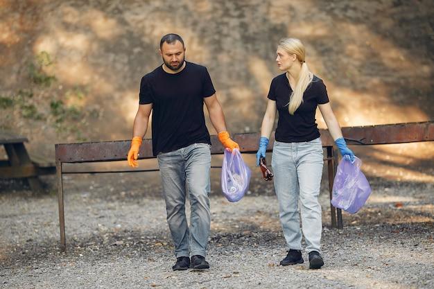 Paar sammelt müll in müllsäcken im park