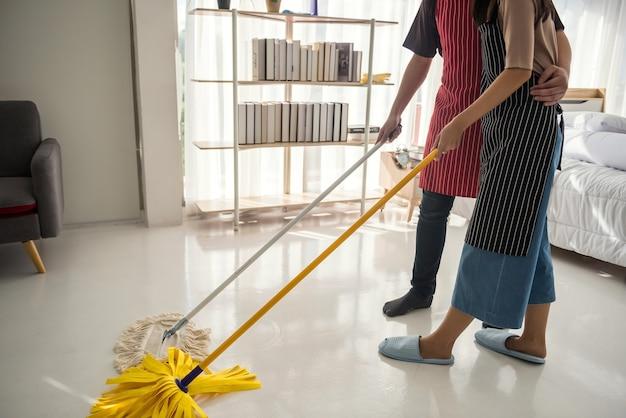 Paar sauberes zuhause schlafzimmer mit staubsauger und mopp. hygiene- und gesundheitslebensstilkonzept.