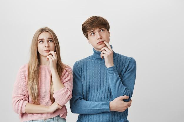 Paar schaut nachdenklich auf. blondes mädchen und kerl denken, wählen
