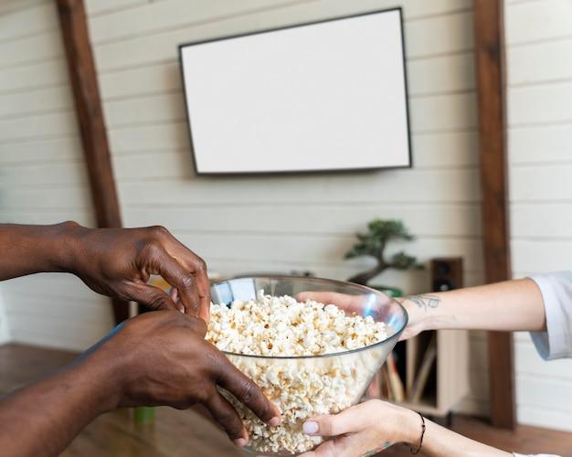 Paar schaut sich einen film an, während es popcorn isst