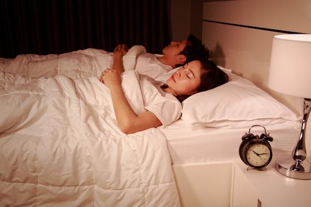 Paar schläft auf einem bequemen bett im schlafzimmer in der nacht