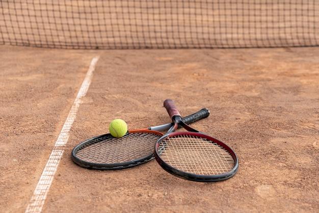 Paar schläger mit tennisball auf dem boden