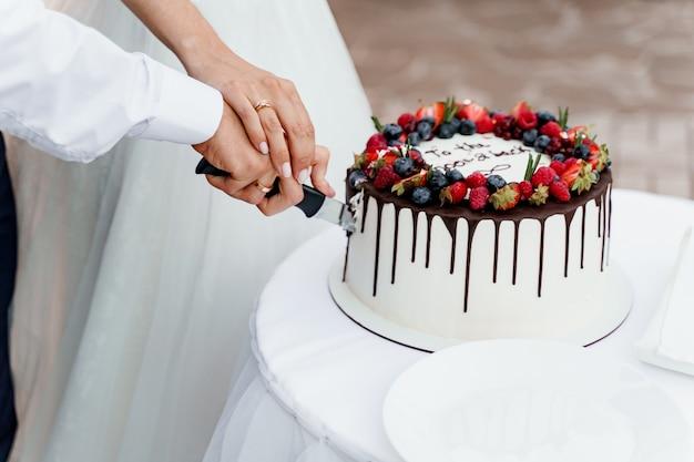 Paar schneidet hochzeitstorte mit erdbeeren und blaubeeren an der spitze.