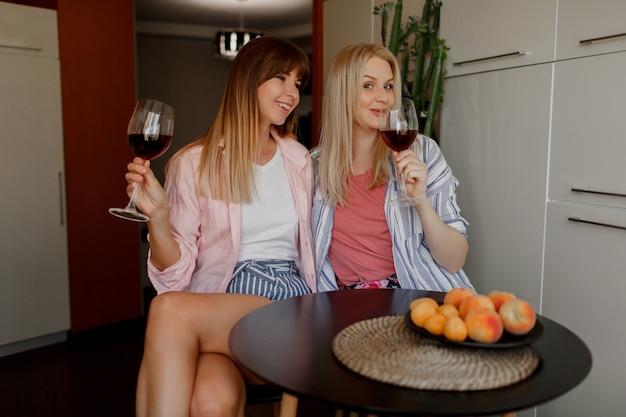 Paar schöne frauen, die wein zu hause trinken. pyjama tragen.