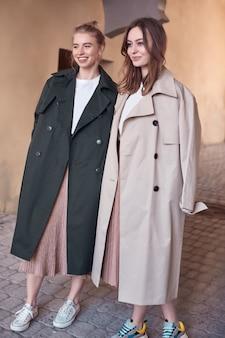 Paar schöne hipster-mädchen, die lange mode-mäntel auf der straße tragen