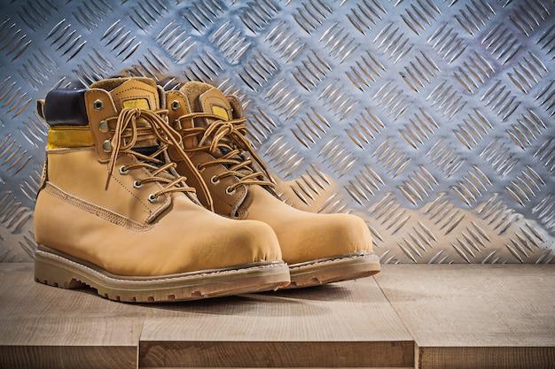 Paar schützende wasserdichte stiefel holzbrett gerillt metallblech baukonzept