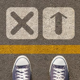 Paar schuhe stehen auf einer straße mit zwei symbol