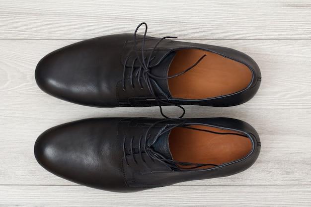 Paar schwarze lederne herrenschuhe auf grauem holzhintergrund. stilvolle und elegante schuhe für herren. ansicht von oben