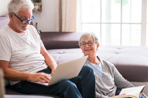 Paar senioren zu hause - mann mit laptop und brille auf dem sofa sitzend - frau sitzt auf dem grund und liest ein buch - innen- und liebeskonzept