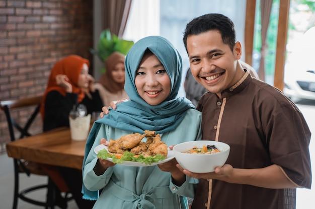 Paar serviert essen für freund und familie