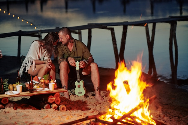 Paar sitzt am feuer am strand