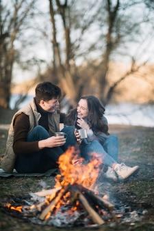 Paar sitzt am lagerfeuer
