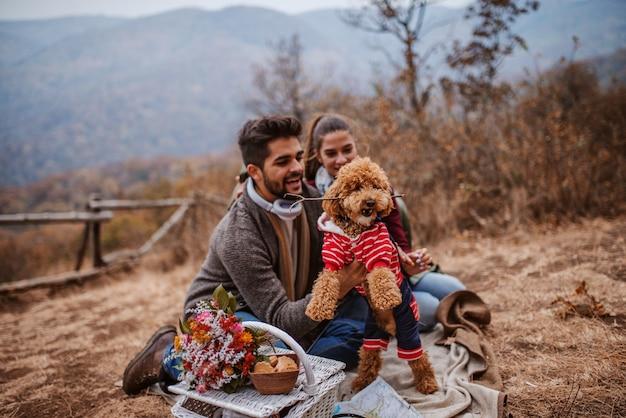 Paar sitzt am picknick und spielt mit dog.poodle