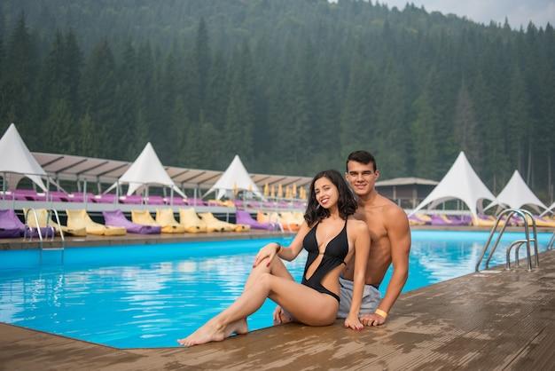 Paar sitzt am rand des pools im luxuriösen resort