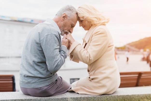 Paar sitzt am rande eines blumenbeets