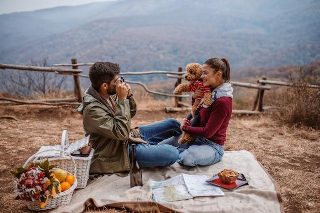 Paar sitzt auf decke beim picknick. mann, der foto seiner freundin und seines hundes macht.