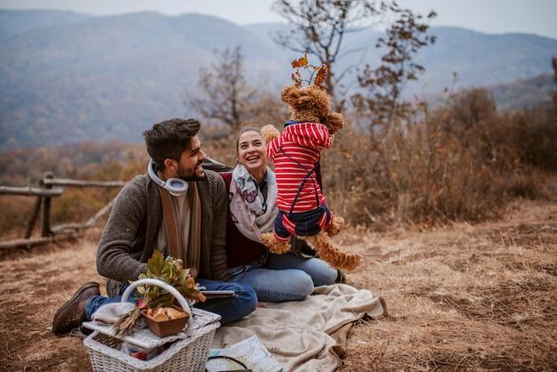 Paar sitzt auf decke beim picknick. mann spielt mit hund.