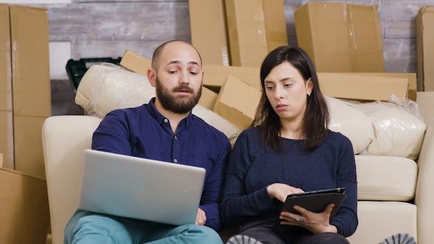 Paar sitzt auf dem boden ihrer neuen wohnung und macht online-shopping auf laptop und tablet.
