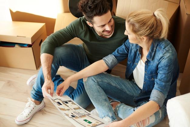 Paar sitzt auf dem boden mit blaupause