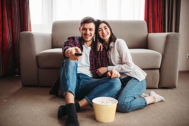Paar sitzt auf dem boden und sieht fern mit popcorn