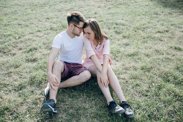 Paar sitzt auf dem rasen mit viel liebe