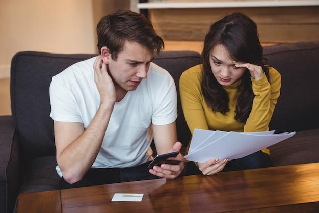 Paar sitzt auf dem sofa und diskutiert mit finanzdokumenten im wohnzimmer