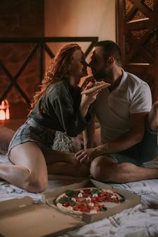 Paar sitzt auf dem teppich und isst pizza
