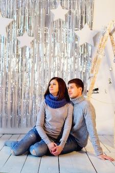 Paar sitzt auf dem weißen holzboden auf silbernem funkeln