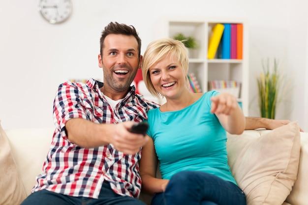 Paar sitzt auf der couch und schaut sich einen lustigen film an