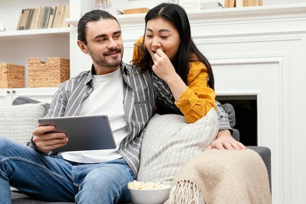 Paar sitzt auf der couch und verbringt viel spaß miteinander