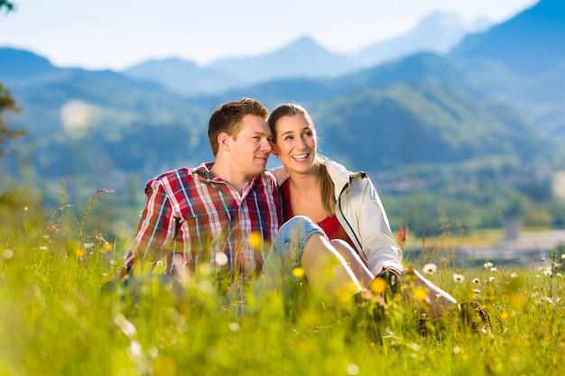Paar sitzt auf der wiese mit berg