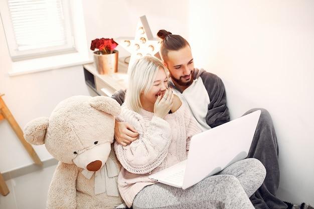 Paar sitzt auf einem bett in einem raum und benutzt einen laptop